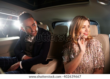 Attractive young couple laughing in the back of a limousine - stock photo