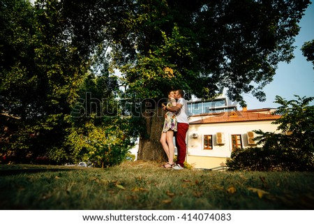 Attractive young couple lovely hugging in the city among trees and looking each other. Photo with copy space at the left - stock photo