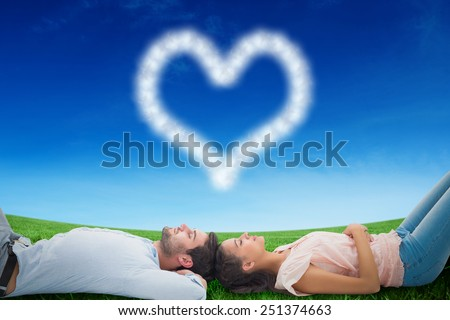Attractive young couple lying down against green field under blue sky - stock photo