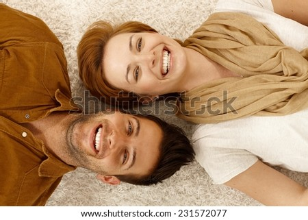 Attractive young couple lying on carpet, looking at camera, smiling happy. Above view. - stock photo