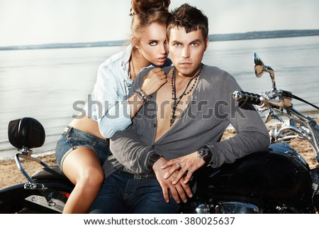 Attractive young couple on a motorcycle. - stock photo