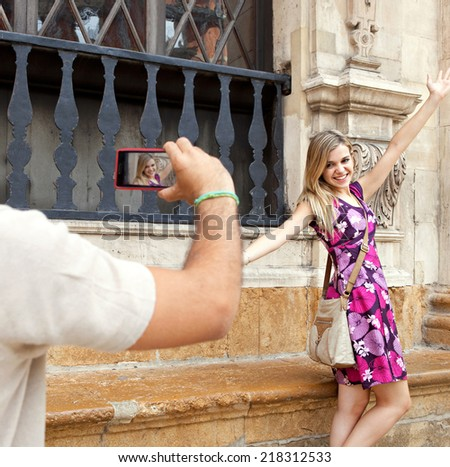 Attractive young couple on holiday, visiting a destination city and taking pictures with a smartphone, outdoors. Travel and technology lifestyle. - stock photo