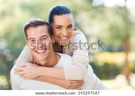 attractive young couple piggybacking outdoors - stock photo