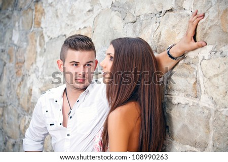 Attractive young couple posing in a stone wall - stock photo