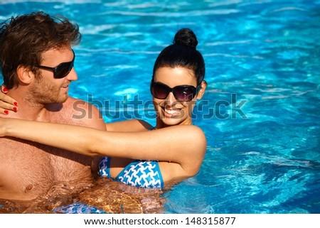 Attractive young couple refreshing in outdoor pool at summertime, smiling. - stock photo