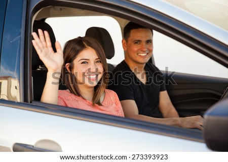 Attractive young couple saying goodbye before driving away in their car - stock photo