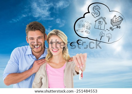 Attractive young couple showing new house key against blue sky - stock photo