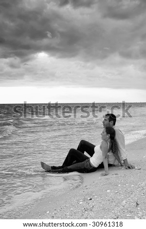 Attractive young couple sitting in the water fully dressed at the beach with big cloud bank overhead looking out over the ocean, finished in black and white - stock photo