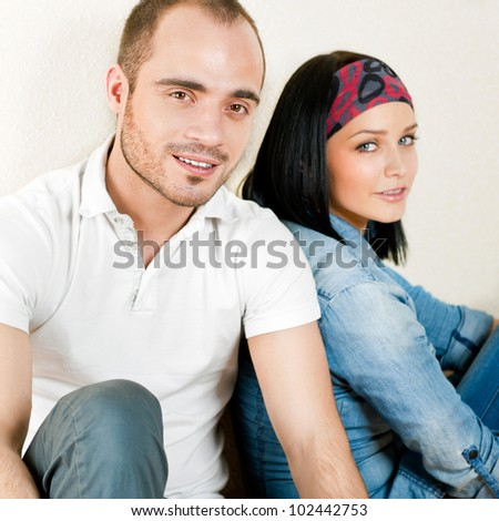 Attractive young couple sitting in their home - stock photo