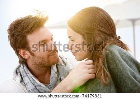 Attractive young couple sitting on beach kissing in summer sunset.? - stock photo