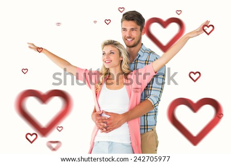 Attractive young couple smiling and embracing against hearts - stock photo