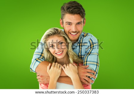Attractive young couple smiling at camera against green vignette - stock photo