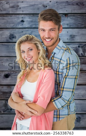 Attractive young couple smiling at camera against wooden background in blue - stock photo
