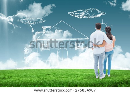Attractive young couple standing with arms around against blue sky over green field - stock photo