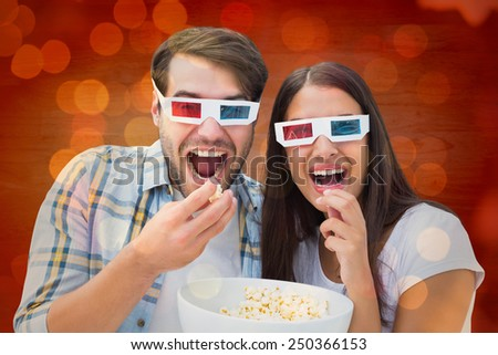 Attractive young couple watching a 3d movie against close up of christmas lights - stock photo