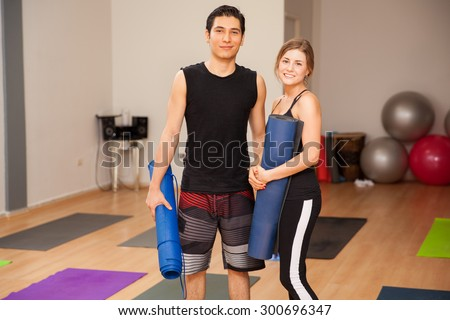 Attractive young couple with exercise mats getting ready for their yoga class together - stock photo