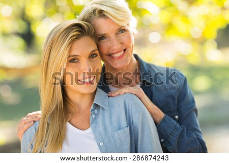 attractive young daughter and middle aged mother outdoors - stock photo