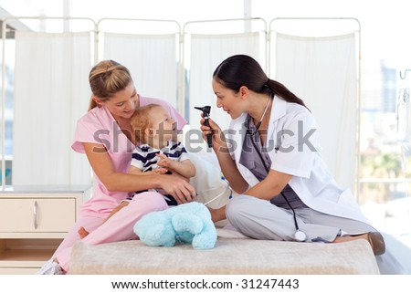 Attractive young doctors attending to a baby - stock photo