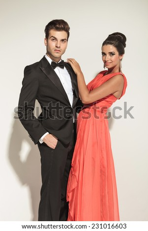 Attractive young elegant business man holding one hand in pocket while his girlfriend is embracing him. - stock photo