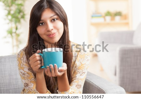 Attractive young ethnic woman in living room holding blue coffee mug wearing festive yellow shirt with flowers. - stock photo