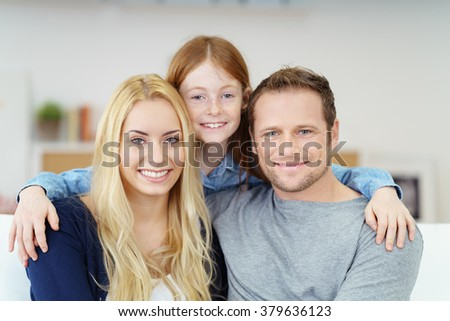 Attractive young family posing close together for a portrait with happy smiles with the young daughter between her parents on a sofa at home - stock photo
