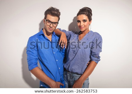 Attractive young fashion man embracing his girlfriend while looking at the camera. - stock photo