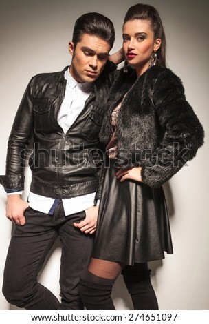 Attractive young fashion man looking down whlie his girlfriend is leaning on him. - stock photo