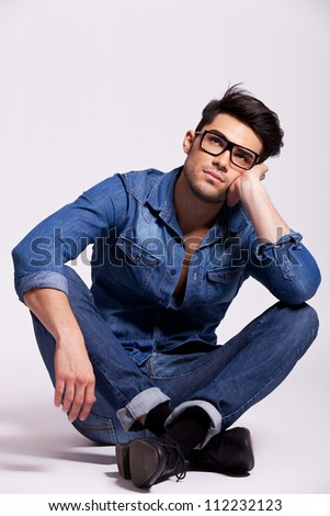 attractive young fashion man wearing glasses, sitting and thinking on a gray studio background - stock photo