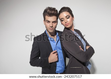 Attractive young fashion woman holding her arms crossed while looking down. Her lover is looking at the camera while fixing his jacket. - stock photo