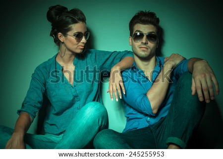 Attractive young fashion woman looking at her lover while he is looking at the camera. - stock photo