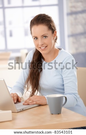 Attractive young female browsing internet at home, sitting at desk, using laptop, smiling.? - stock photo