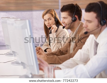 Attractive young female customer servicer working in callcenter.? - stock photo