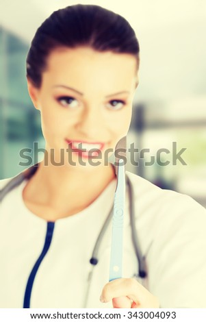 Attractive young female doctor with scalpel - stock photo