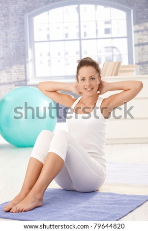 Attractive young female doing exercises on floor at home, smiling.? - stock photo
