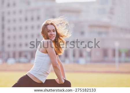 Attractive young female in sportswear stretching in urban scenery. Wind flutters hair. Vintage coloring. Copy space. Concept of healthy lifestyle in a city - stock photo
