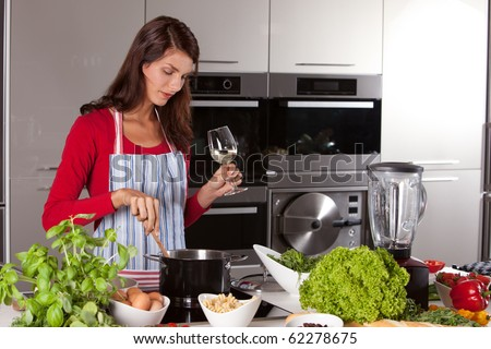 Attractive young female in the kitchen stirring in the pan while drinking wine - stock photo
