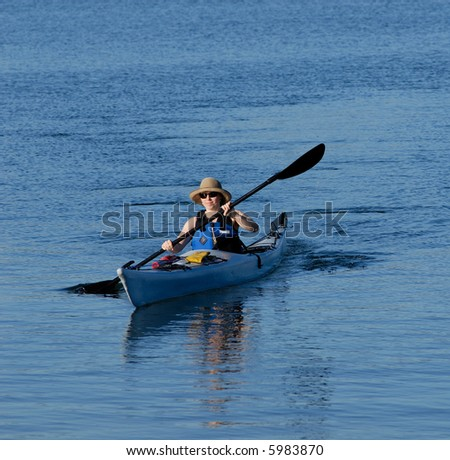 Attractive young female kayaker is rowing in deep blue sub-tropical waters of Mission Bay, San Diego, California. - stock photo