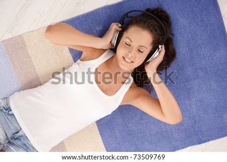 Attractive young female laying on floor at home, listening to music through headphones, smiling, eyes closed. - stock photo