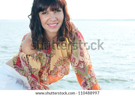 Attractive young female near the shore, smiling and looking at camera - stock photo