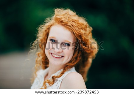 Attractive Young Female Redhead, smiling with hair blowing - stock photo