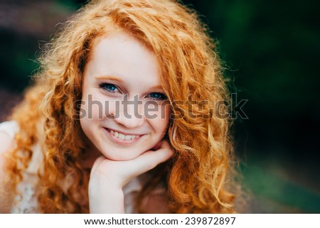 Attractive Young Female Redhead, smiling with hand on chin - stock photo