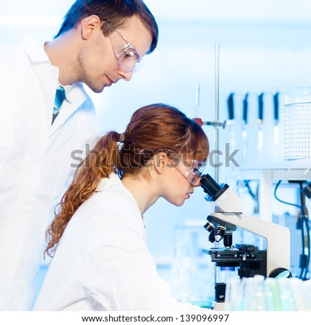 Attractive young female research scientist and her post doctoral male supervisor looking at the microscope slide in the life science (forensics, microbiology, biochemistry, genetics, ) laboratory. - stock photo