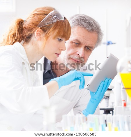 Attractive young female scientist and her senior male supervisor checking experiment protocol at tablet laptop computer in the life science research laboratory (genetics, forensics, microbiology..) - stock photo