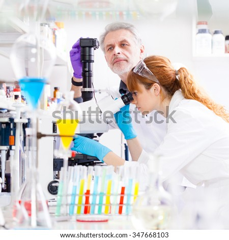 Attractive young female scientist and her senior male supervisor looking at the microscope slide in the life science research laboratory. Bichemistry, genetics, forensics, microbiology... - stock photo