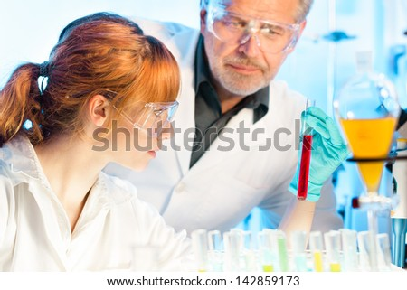 Attractive young female scientist and her senior male supervisor observing color shift of a red liquid in the glass tube in the life science research laboratory (biochemistry, genetics, forensics,..) - stock photo