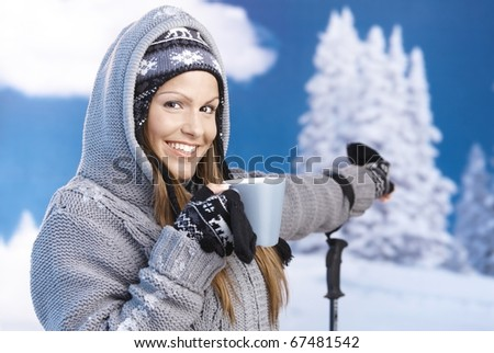 Attractive young female skiing, resting, drinking hot tea, pointing to winter landscape, smiling. - stock photo