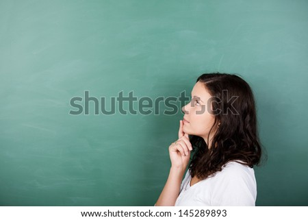 Attractive young female student standing solving a problem staring thoughtfully up into the air with her finger to her lips against a blank green blackboard with copyspace - stock photo