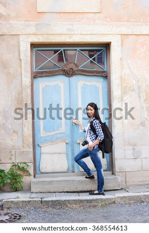 Attractive young female tourist opening door to a hostel - stock photo
