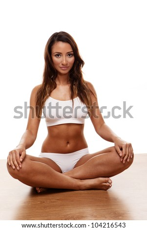 Attractive young female with legs crossed on white background - stock photo