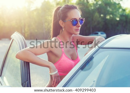 Attractive young fit woman wearing sunglasses standing by her car smilling showing v-sign, victory gesture or peace outdoors portrait. - stock photo